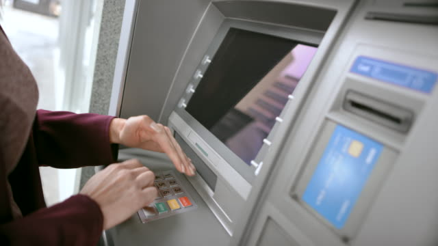 ld woman inserting her bank card and shielding the keypad while entering pin - banks and atms stock videos & royalty-free footage
