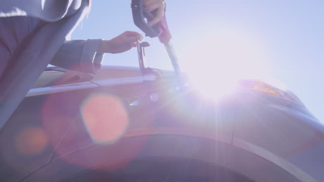 Woman Inserting Nozzle into Car Tank video