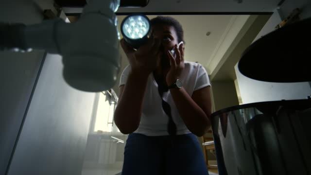 vidéos et rushes de femme plomberie inspection et parler au téléphone - cuisine non professionnelle
