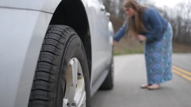 vídeos de stock e filmes b-roll de woman inspects a flat or damaged tire on the rear of her suv on the road - puxar