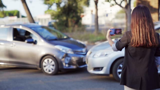 Woman insurance agent taking photo of car accident on mobile phone. A female registers car damage on her smartphone. 4K UHD Woman insurance agent taking photo of car accident on mobile phone. A female registers car damage on her smartphone. 4K UHD. car accident stock videos & royalty-free footage