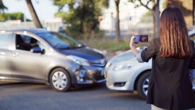 kvinna försäkrings agent tar foto av bil olycka på mobil telefon. en kvinna registrerar bil skador på sin smartphone. 4k uhd - försäkring bildbanksvideor och videomaterial från bakom kulisserna