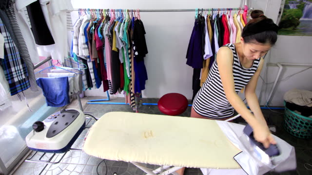 Woman ironing with steam iron at home, time lapse video