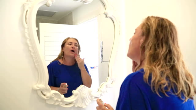Woman is applying cream to her face video