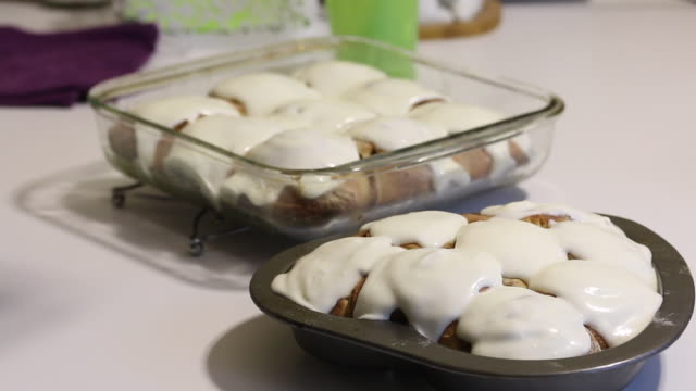 a woman is applying glaze on baked cinnabons. rosy buns are on baking sheets - formare pane video stock e b–roll