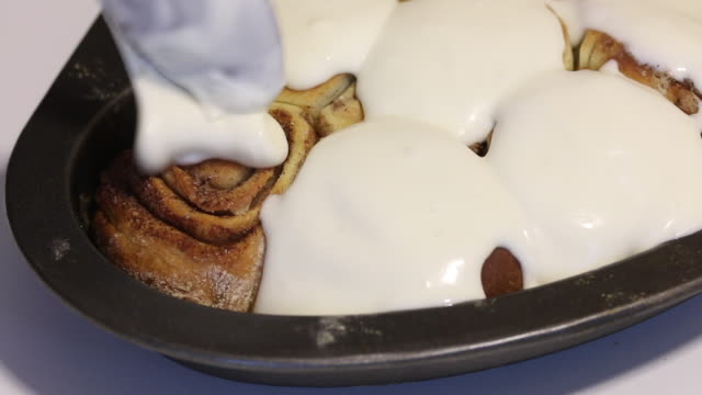 a woman is applying glaze on baked cinnabons. rosy buns are on baking sheets. close-up shot. - formare pane video stock e b–roll