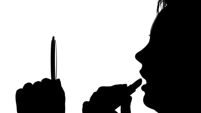 Woman is applying lipstick video