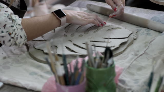 A woman is applying the pattern onto the clay. The woman has a smart watch. video