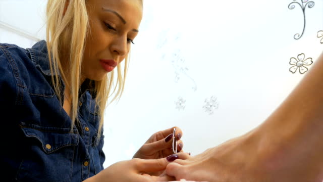 Woman is attended by specialist performing professional pedicure at beauty parlor video