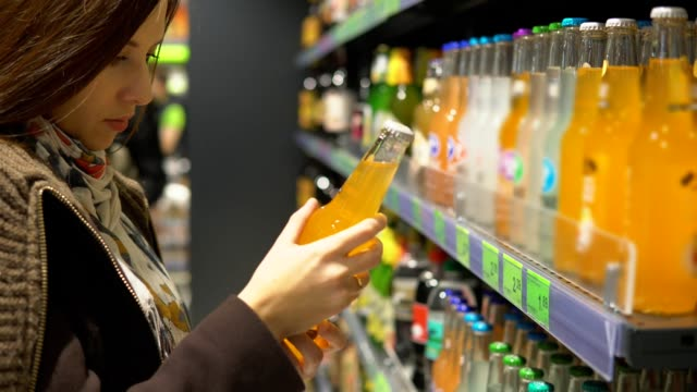 a woman is buying a drink in a bottle in a store. - healthy green juice video stock e b–roll