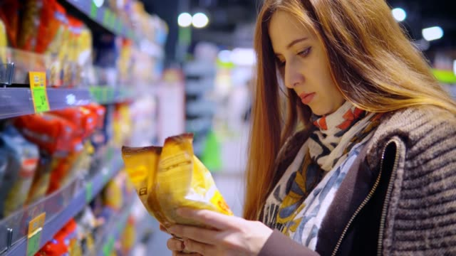 A woman is buying macaroni in a store. video