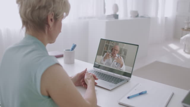 woman is calling doctor by video conference from home, aged experienced professor of medicine is answering on her questions