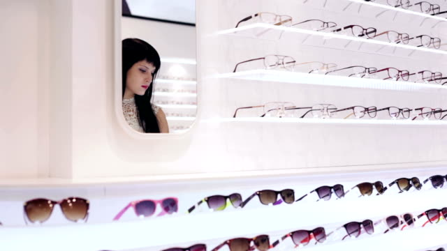Woman is choosing a pair of glasses in optic shop video