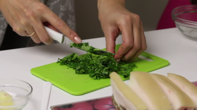 A woman is chopping parsley. Lard lies nearby. Salted lard with herbs and spices.