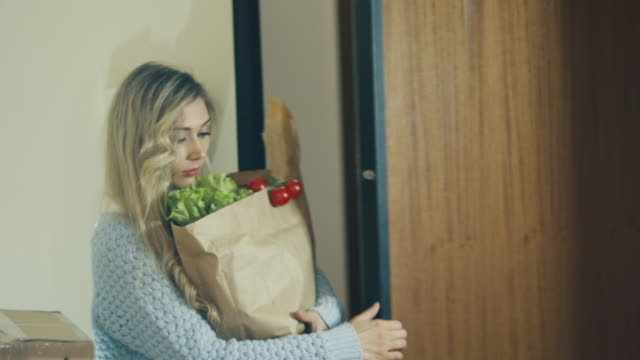 woman is coming to home. holding bag with food in hands. shot on red cinema camera in 4k (uhd). - grocery home video stock e b–roll