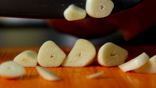 Woman is cutting garlic close-up in the kitchen - video