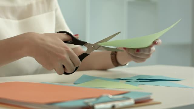 donna taglia carta verde usando forbici - forbici video stock e b–roll
