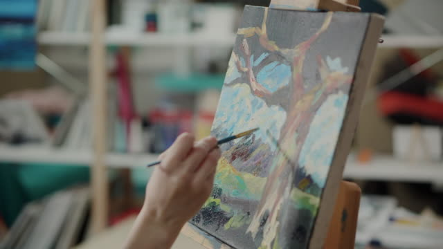 Woman is depicting landscape on canvas by acrylic paints in studio