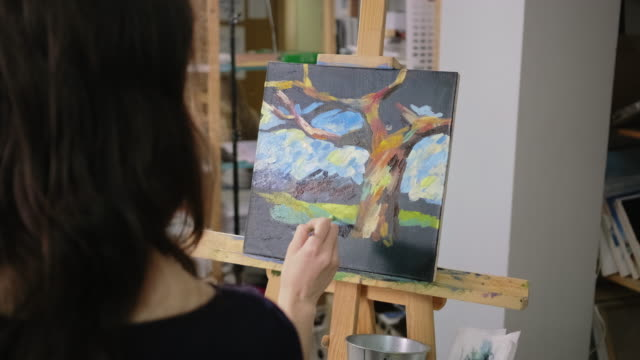 Woman is depicting landscape on canvas in art therapy class, view from back