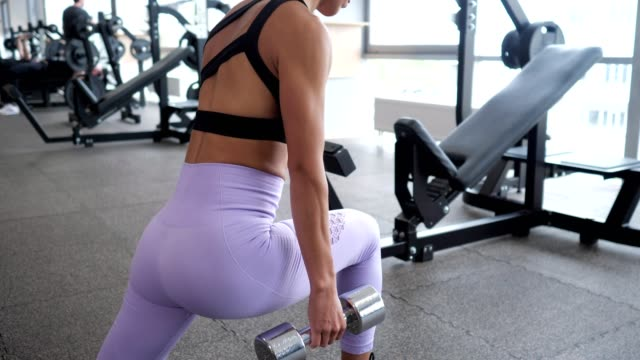 Woman is doing lunges for legs with dumbbells in her hands in gym.