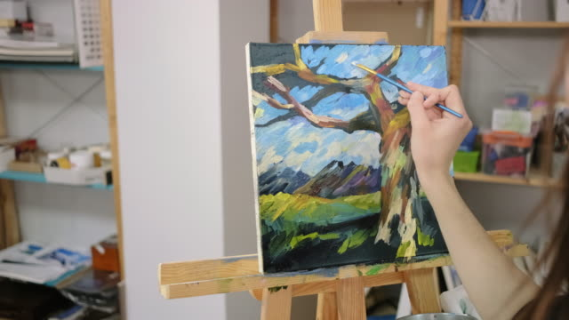 Woman is drawing by wide strokes of paints on canvas, depicting landscape