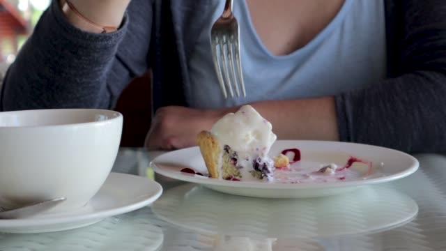 a woman is eating a dessert with an ice cream, using a fork. - nadziewany placek filmów i materiałów b-roll