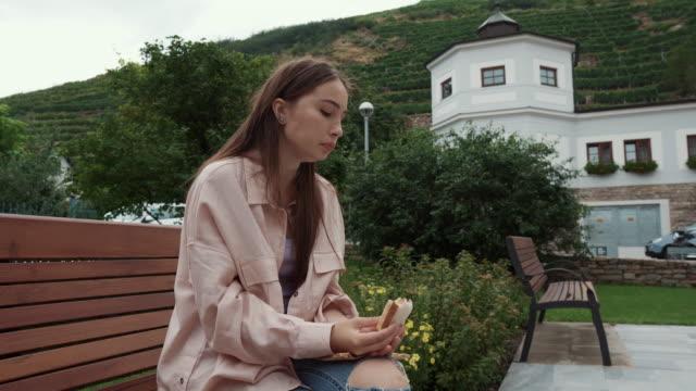 女性は庭のベンチに座ってサンドイッチを食べている - ベンチ点の映像素材/bロール