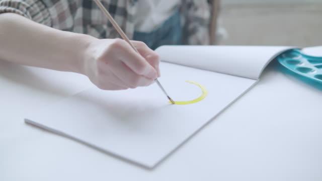 a woman is engaged in art, paints a picture with a brush and paints - pochodzenia rosyjskiego filmów i materiałów b-roll