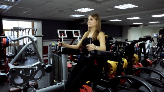 Woman is engaged in gym on exercise equipment on raising legs video