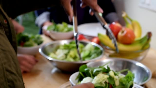 Woman is filling salad bowls and handing them to guests at dinner party