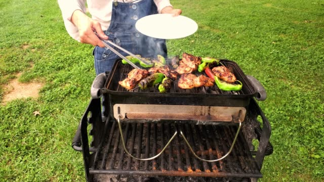 A woman is flipping peppers and chicken that are sizzling on charcoal grill