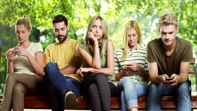 Woman is getting bored while all his friends looking at phone video