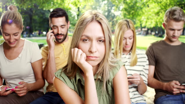 Woman is getting bored while all his friends looking at phone Young Woman is getting bored while all his friends looking at phone ignoring stock videos & royalty-free footage