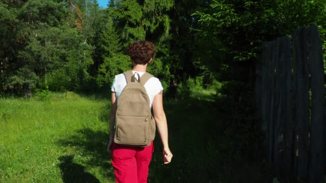 Woman is going for a walk to the forest