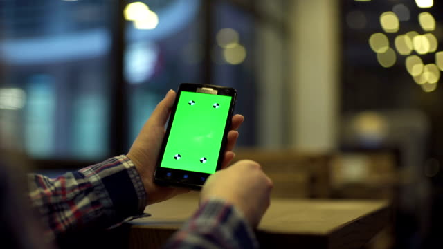 Frau ist Holding Smartphone mit Greenscreen im café – Video