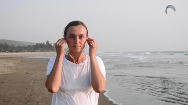 woman is jogging on the sea beach and putting earphones to listen music. - maglietta bianca video stock e b–roll