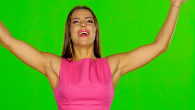 Woman is laughing and throwing money in air. Green screen. Close up video