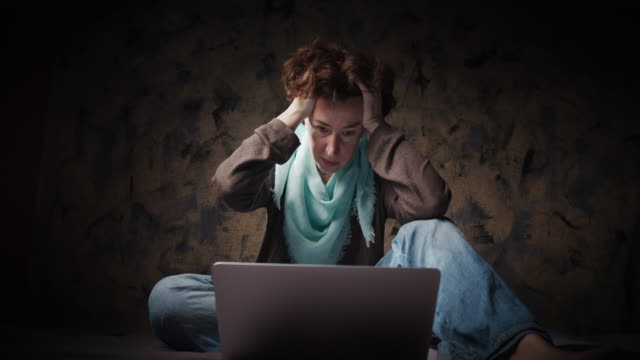 Woman is looking at laptop  screen and thinking