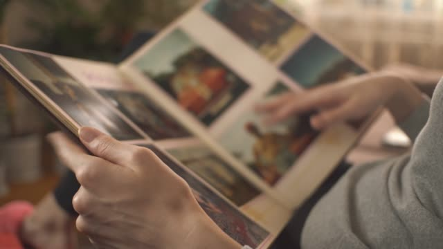 kvinnan tittar på gamla fotoalbum hemma. en kvinna minns det förflutna, som det var innan. - fotografi bild bildbanksvideor och videomaterial från bakom kulisserna