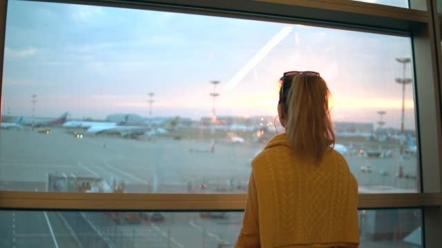 Woman is looking at the take-off site of the airport