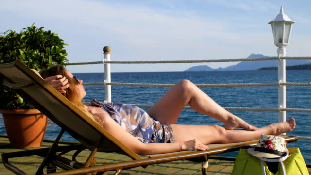 woman is lying on a lounger on a pier, sea surface and silhouette of mountains are in background woman is lying on a lounger on a pier, windy weather, soft sunshine, sea surface and silhouette of mountains are in background, near flowerbed with green plant, white ropes, street lamp, vivid hat and beach bag lounge chair stock videos & royalty-free footage