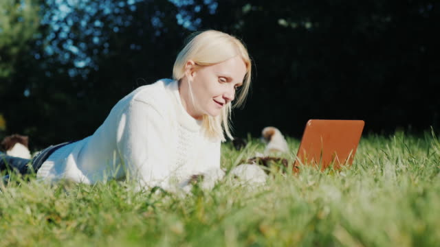 A woman is lying on the lawn, using a laptop. Next run around small puppies video