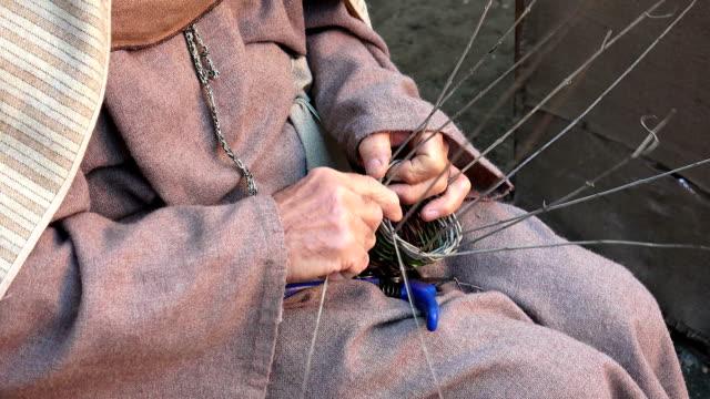 woman is making a woven wicker basket - halmslöjd bildbanksvideor och videomaterial från bakom kulisserna