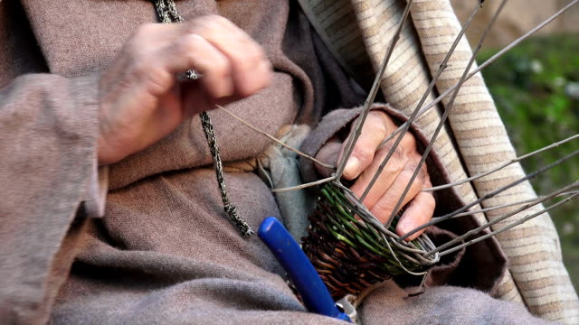 woman is making a woven wicker basket