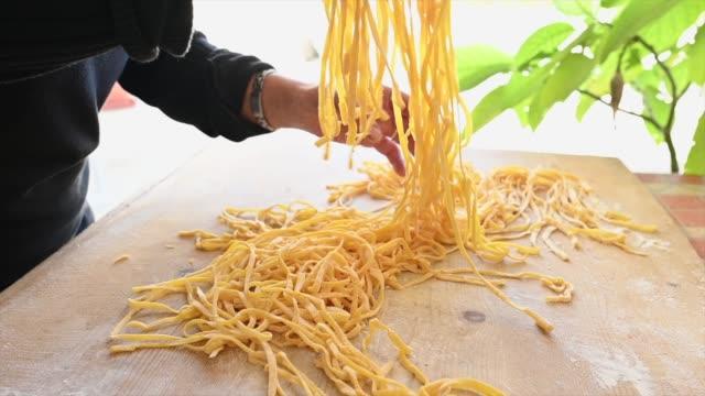 Una mujer está haciendo pasta fresca llamada 'Tallarines' de huevos frescos y harina de trigo durum. Fettuccine es una pasta plana gruesa popular en la cocina romana y la Toscana. - vídeo