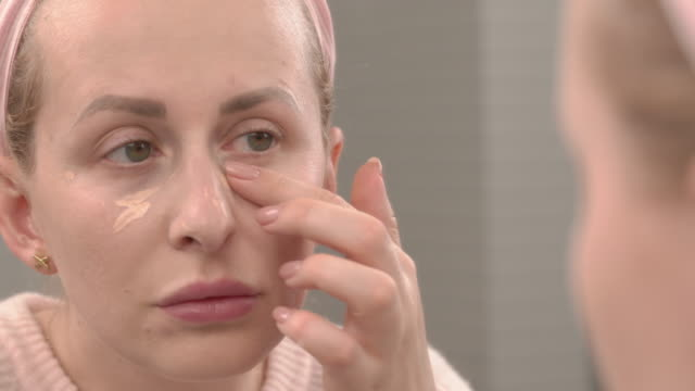 a woman is making herself a make-up. she uses a concealer. makeup at home. - comparsa video stock e b–roll
