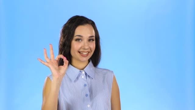 woman is making ok gesture and winking - znak ok filmów i materiałów b-roll