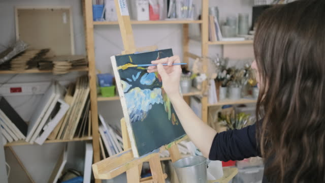 Woman is making strokes by artistic brush with oil paints, closeup