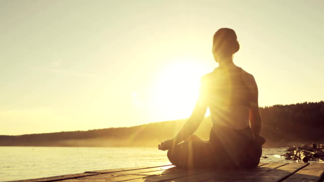 Woman is meditating in Lotus Pose sitting on pier near the river at sunset