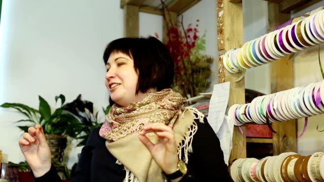 kvinna erbjuder färgglada satinband till sin kund. - blue yellow band bildbanksvideor och videomaterial från bakom kulisserna